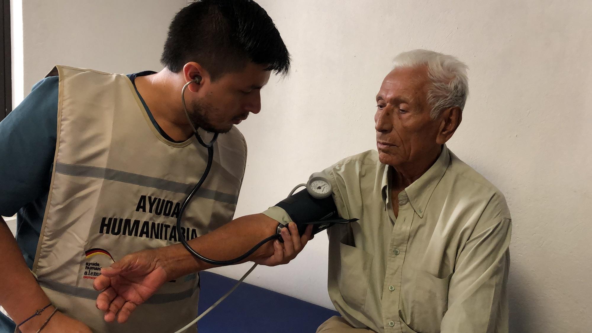 Ein Mitarbeitender unserer Partnerorganisation misst den Blutdruck eines älteren Herren