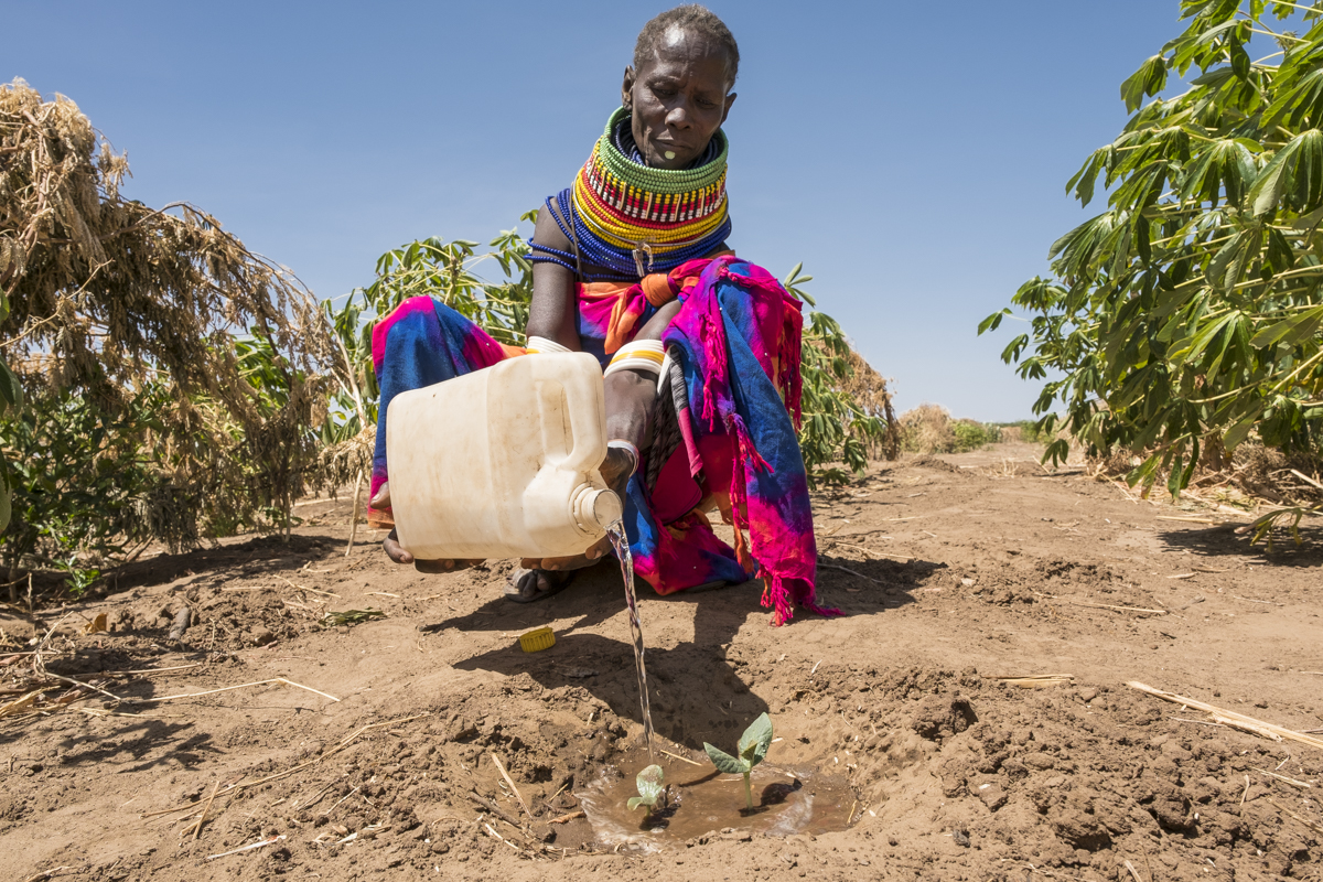 A woman with a water canister on her field
