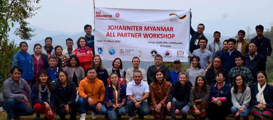 Teilnehmende des Workshophs in Myanmar stehen vor dem Johanniter Logo