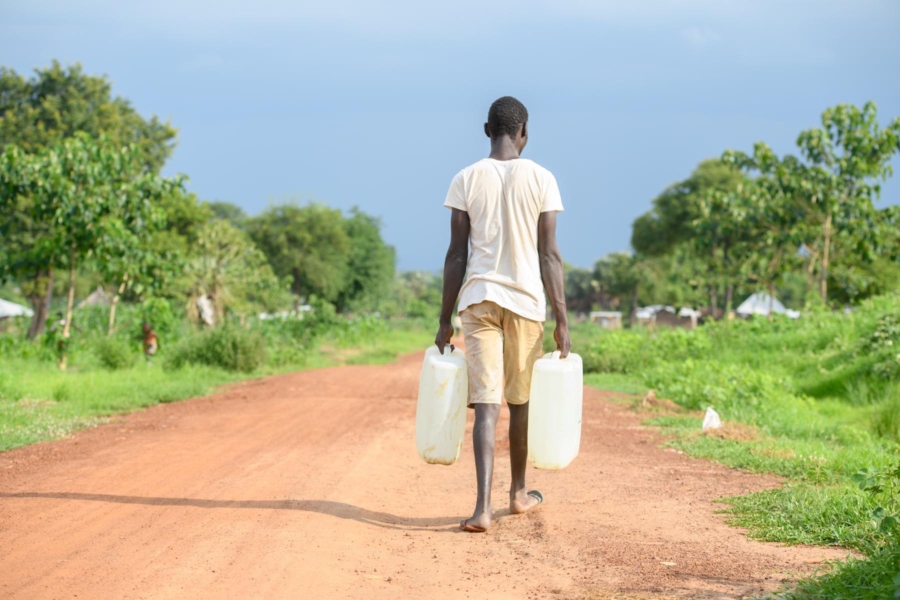 Lomuju geht mit einem Wasserkanister eine Straße entlang.