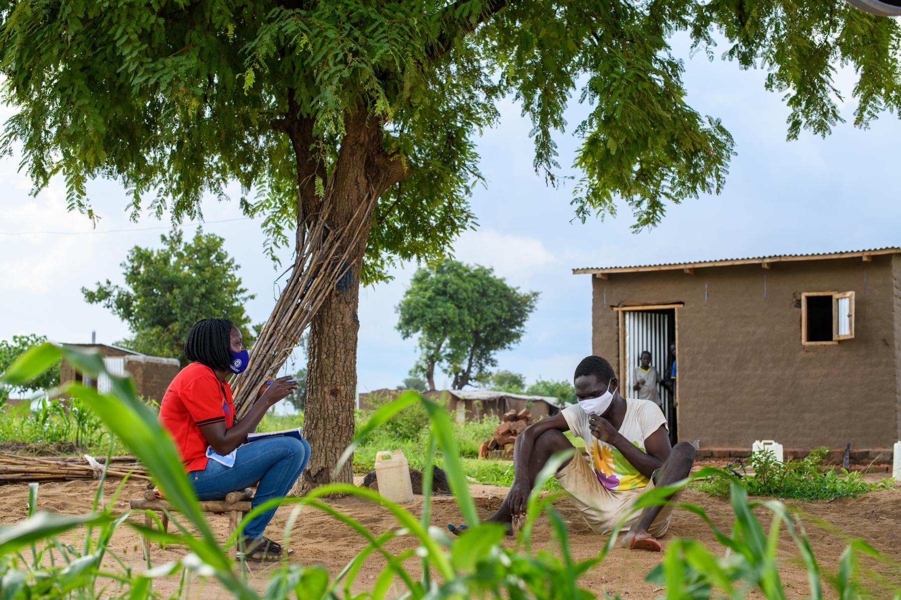 Lomuju sitzt auf dem Boden und Joyce auf einem Stuhl einer vor einer Hütte