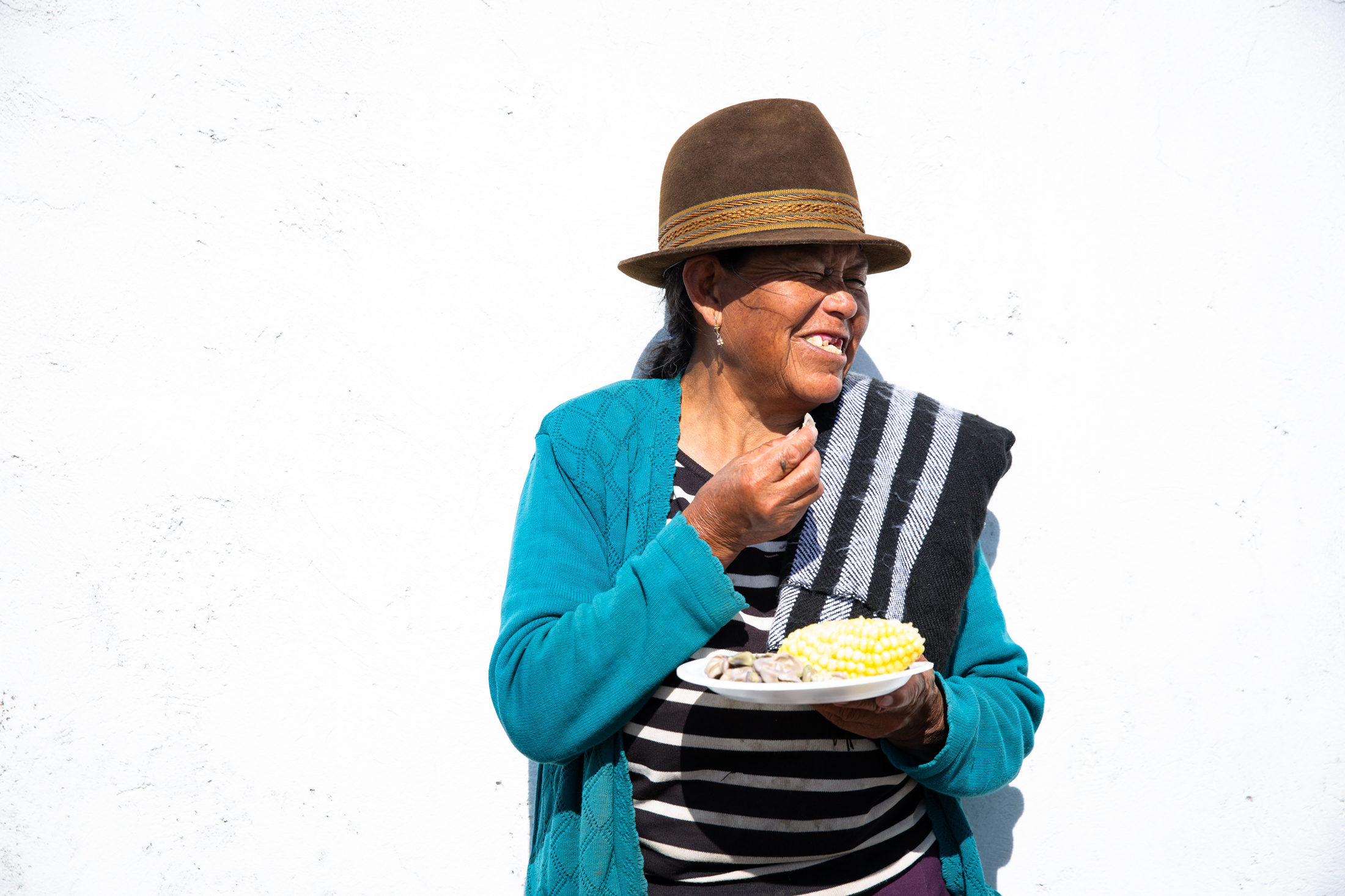 A happy woman eating corn