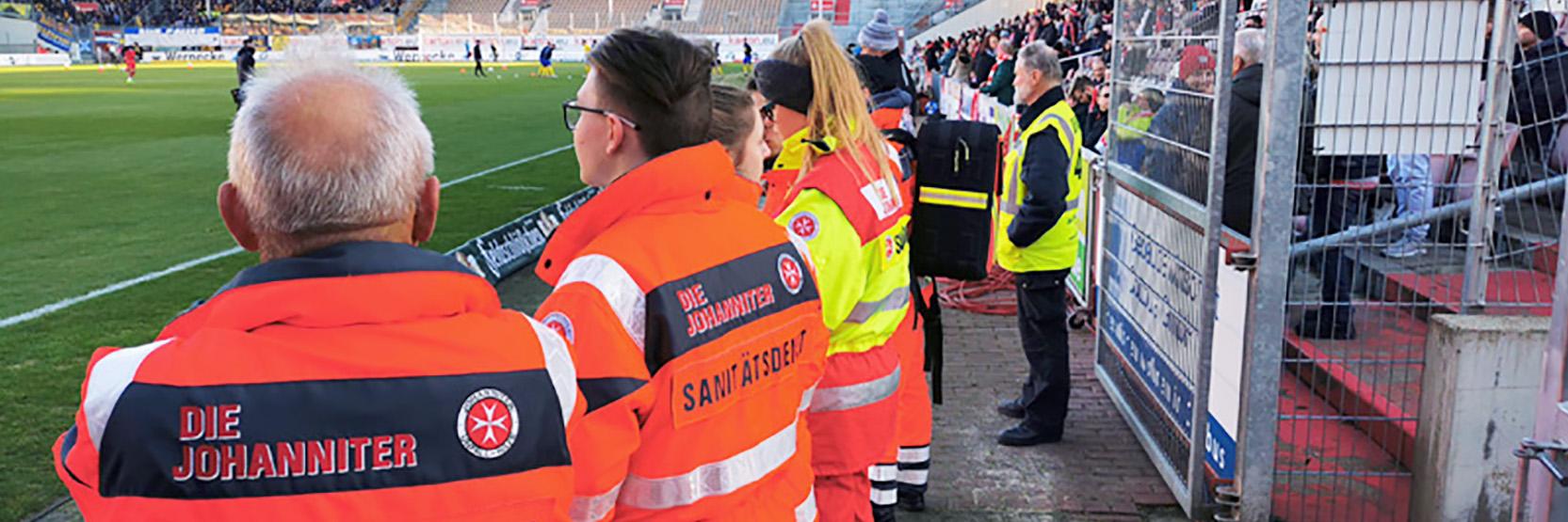 Ehrenamtliche Helfer des Sanitätsdienstes bei einer Absicherung eines Fußballspiels.