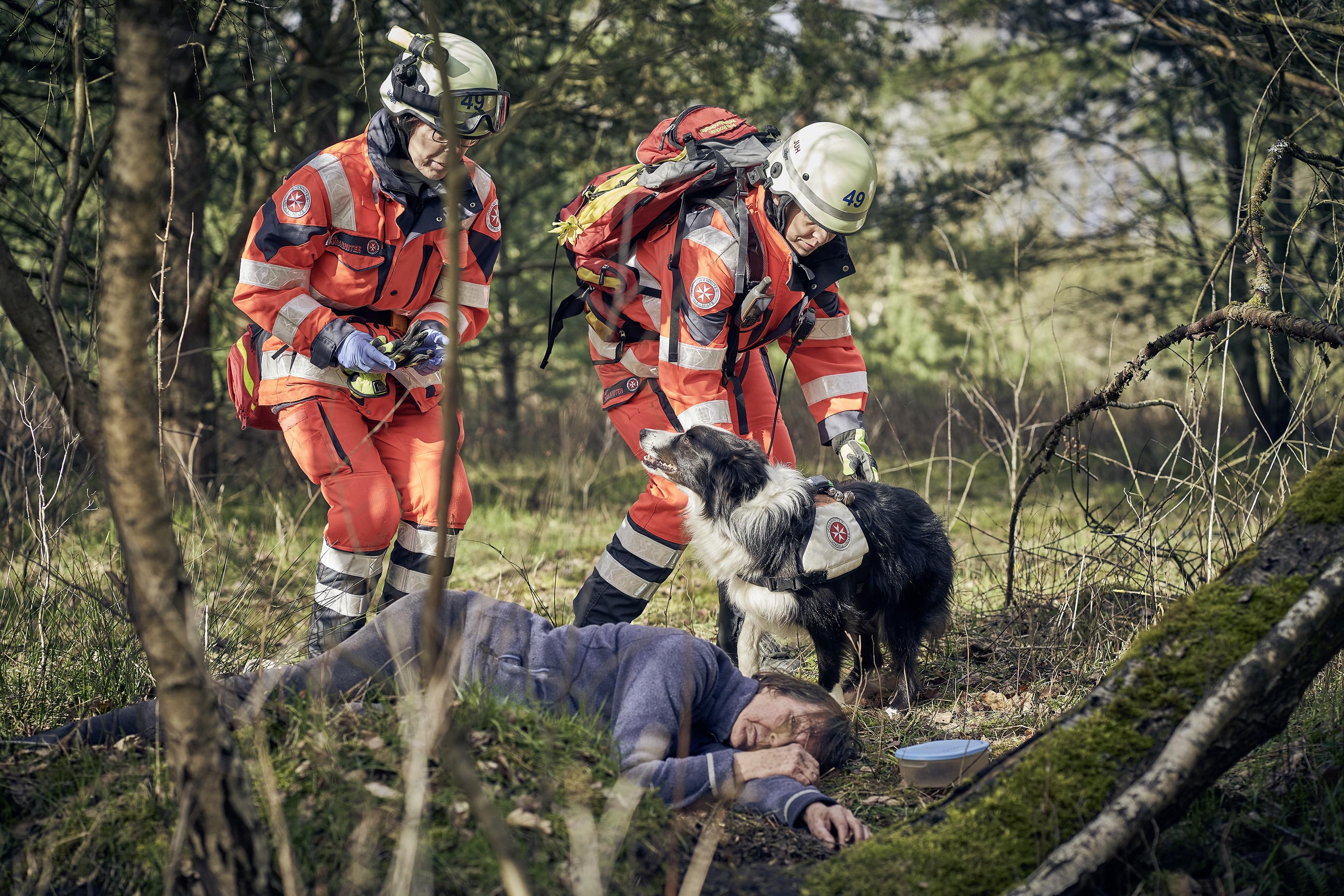 Zwei Personen der Rettungshundestaffel und ein Rettungshund finden eine in Not geratene Person im Wald