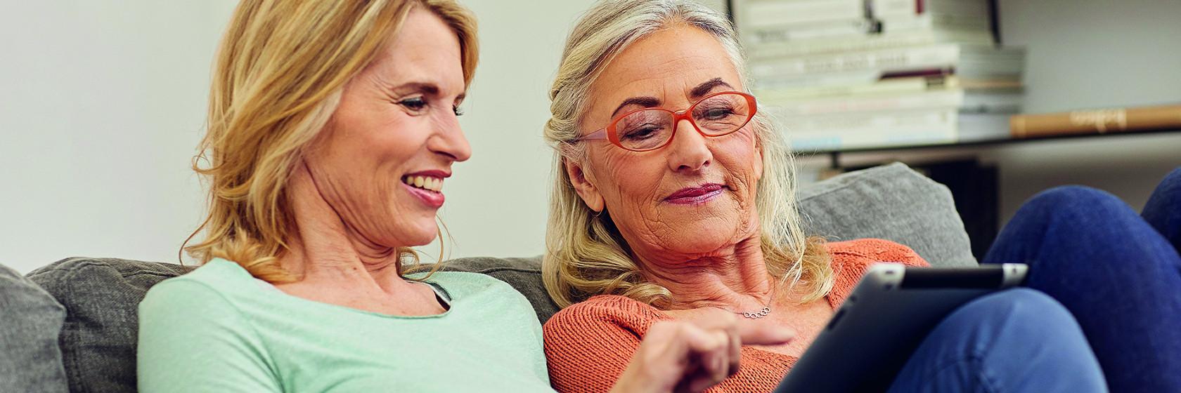 Zwei Frauen schauen auf einen Tablet-Computer.