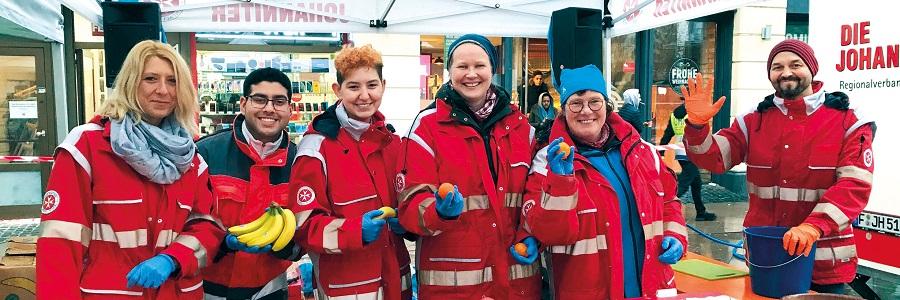 Ehrenamtliche Helfer teilen frisches Obst und Stollen an Bedürftige und Obdachlose aus