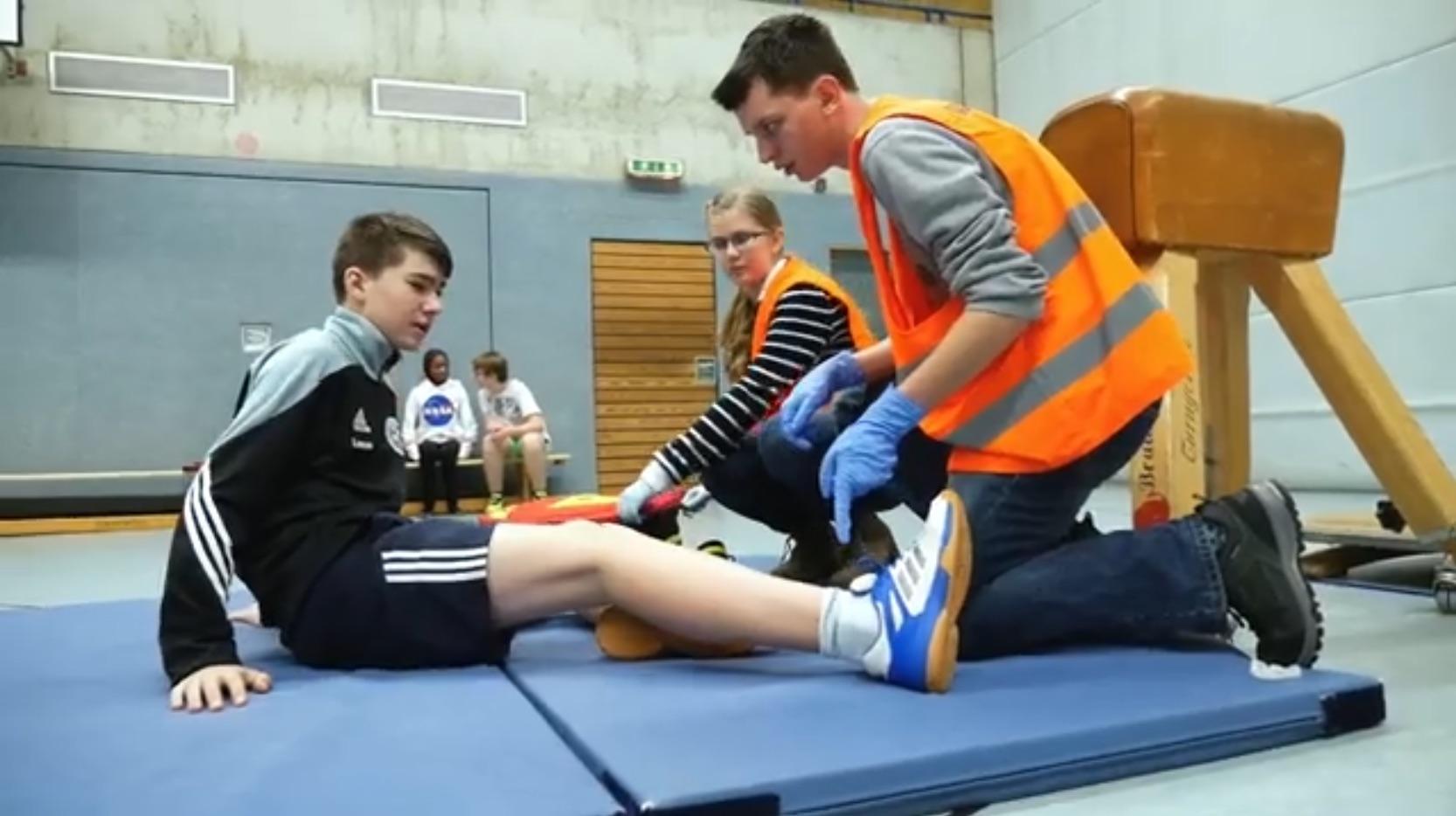 Ein Junge sitzt auf einer Sportmatte und wird von Schulsanitäter*innen versorgt.
