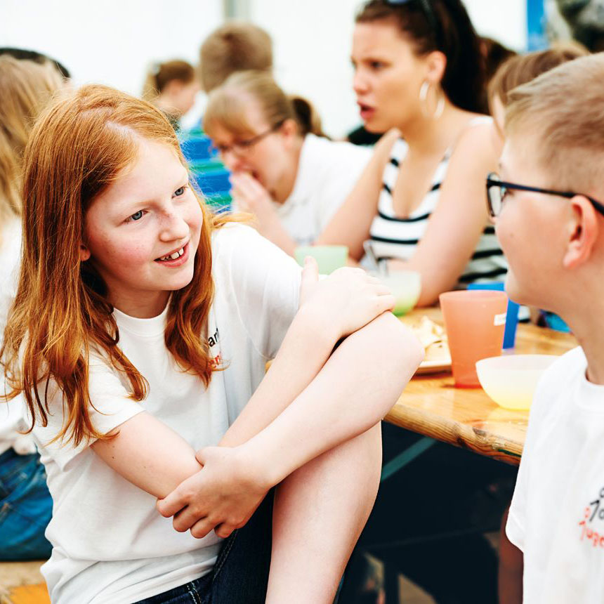 Ein Mädchen sitzt an einer Bierzeltgarnitur und lacht einen Jungen an, der ihr zuhört.