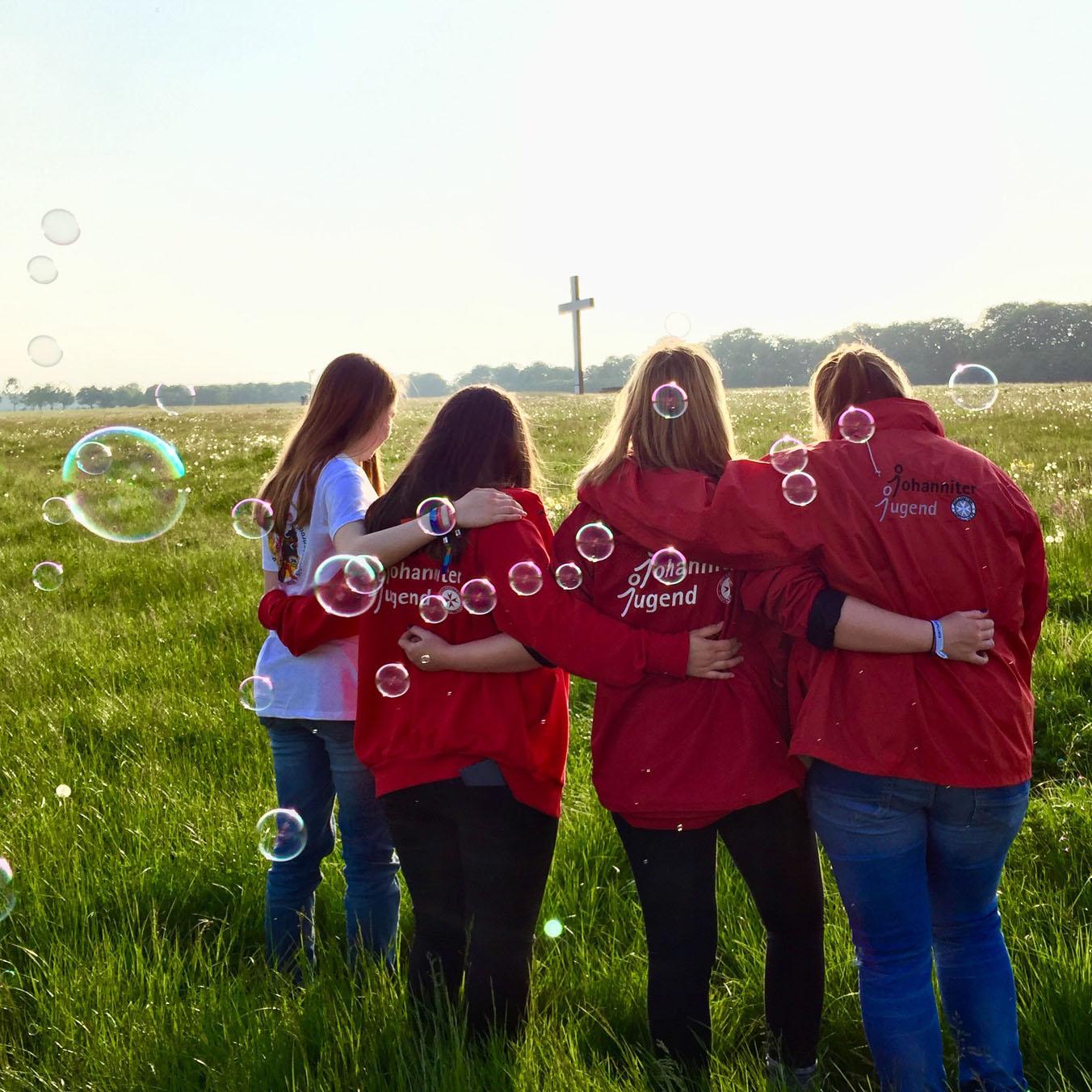Vier Jugendliche mit Johanniter-Jugend-Jacke stehen Arm in Arm auf einer großen Wiese. Im Hintergrund ist ein großes Kreuz zu sehen.