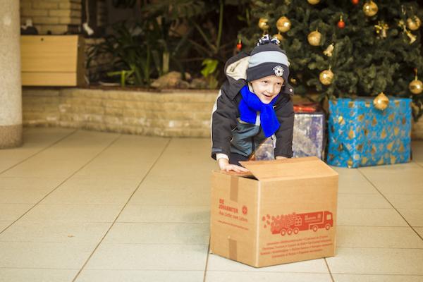 Glücklicher Junge schiebt ein Weihnachtstrucker Paket über den Boden