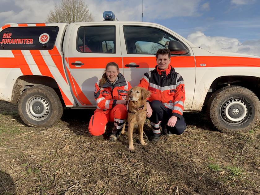Eine Johanniterin und ein Johanniter mit Hund knien vor einem Einsatzfahrzeug