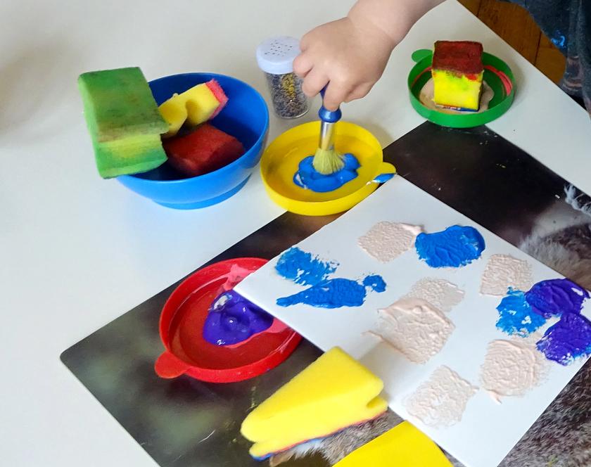 Ein Kind tupft mit einem Schwamm bunte Farbe auf ein Blatt Papier