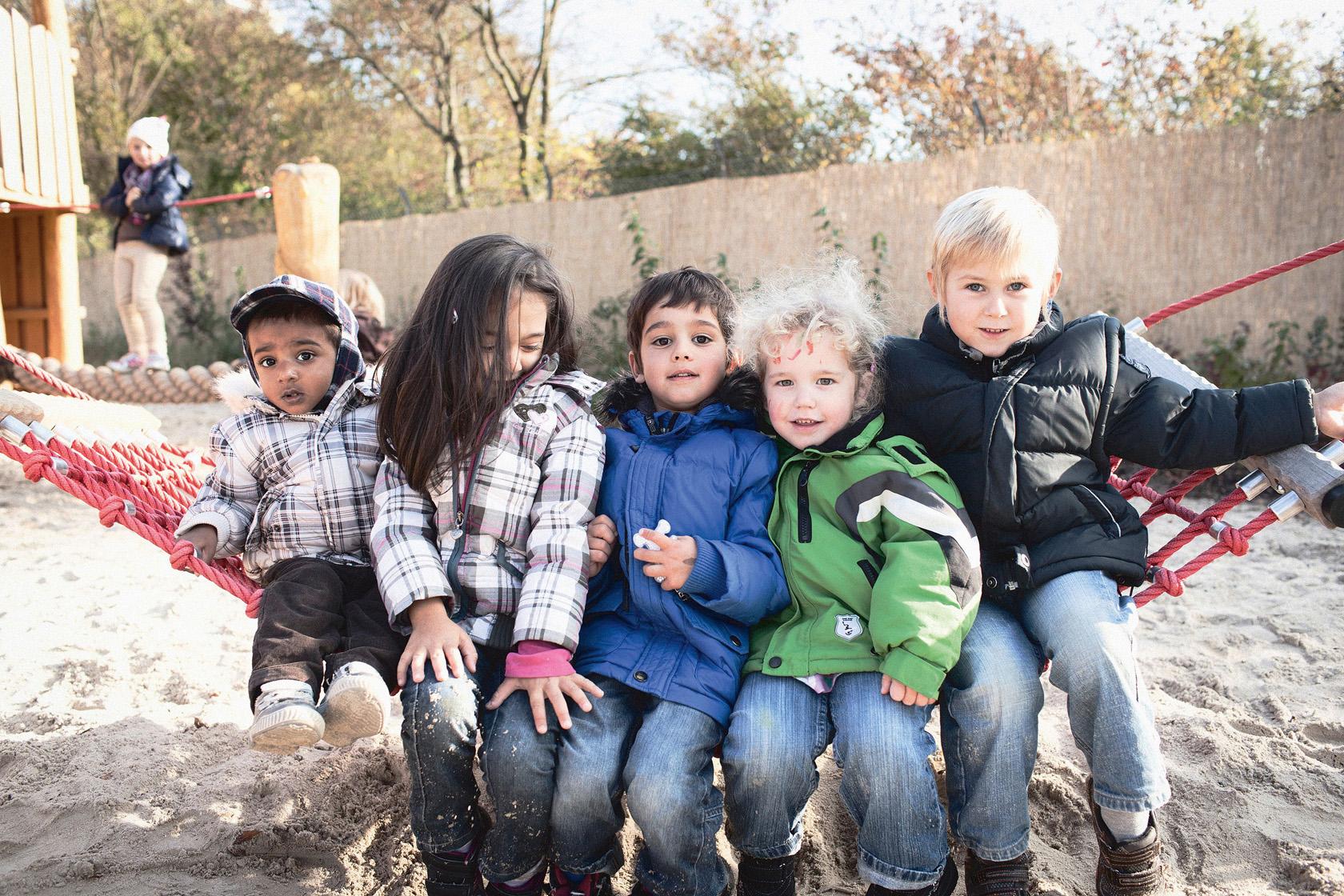 5 Kinder auf einem Seil sitzend