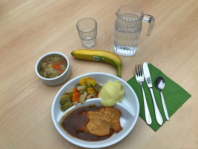 Teller mit Schnitzel, Kartoffelbrei, Gemüse, Besteck ein Glas Wasser