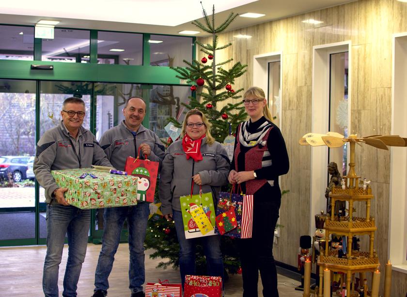 Johanniterinnen und Johanniter mit Geschenken vor dem Wunschbaum (Tannenbaum mit kleinen Anhängern auf dem die Wünsche der Kinder stehen).