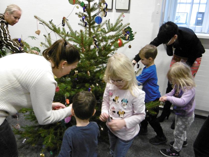 Kinder und Erwachsene dekorieren den Weihnachtsbaum liebevoll mit selbstgemachten Christbaumkugeln.