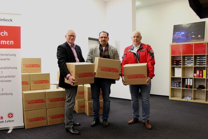Dienststellenleiter und Mitglieder der Freimaurerloge präsentieren die Pakete.