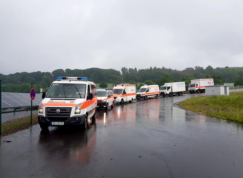 Sechs Johanniter-Fahrzeuge fahren in einer Reihe über eine nasse Straße