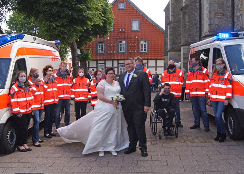 Lukas Hennemann und seine Frau stehen in Hochzeitskleidung neben zwei Einsatzfahrzeugen und den Johanniter die ihnen zur Vermählung gratulierten.