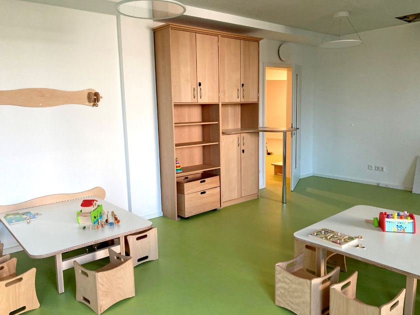 Grüner Fußboden, kleine Tische mit kleinen Stühlen inkl. Armlehnen. Auch ein Regal zum Aufbewahren von Spielsachen ist zu sehen.