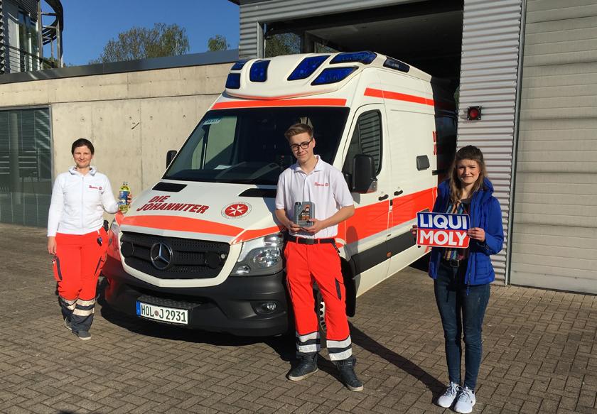 Drei Mitarbeitende der Johanniter aus Holzminden stehen vor einem Einsatzfahrzeug und zeigen Produkte von Liqui Moly.
