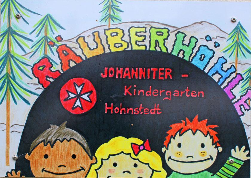 Türschild der Kita Räuberhöhle in Hohnstedt mit der Zeichungen von drei Kindern, dem Johanniter-Logo und einem kleinen Wald im Hintergrund.