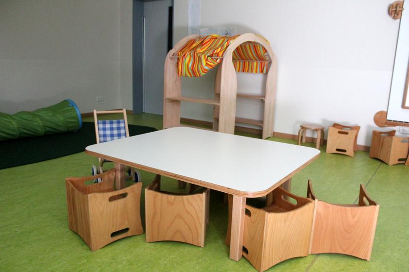 Kleiner Holztisch mit Stühlen zum Spielen. Im Hintergrund ist ein Teil der Puppenecke zu sehen.