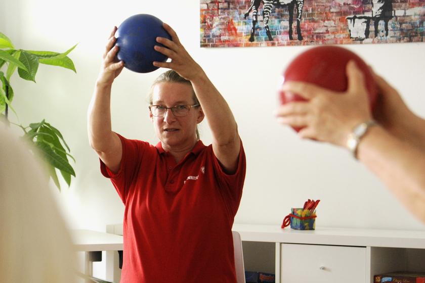 Lara Henne, Leiterin des Quartierstreffs im Q4 und ehemalige Sportstudentin zeigt die sportlichen Übungen mit einem Gymnastikball.