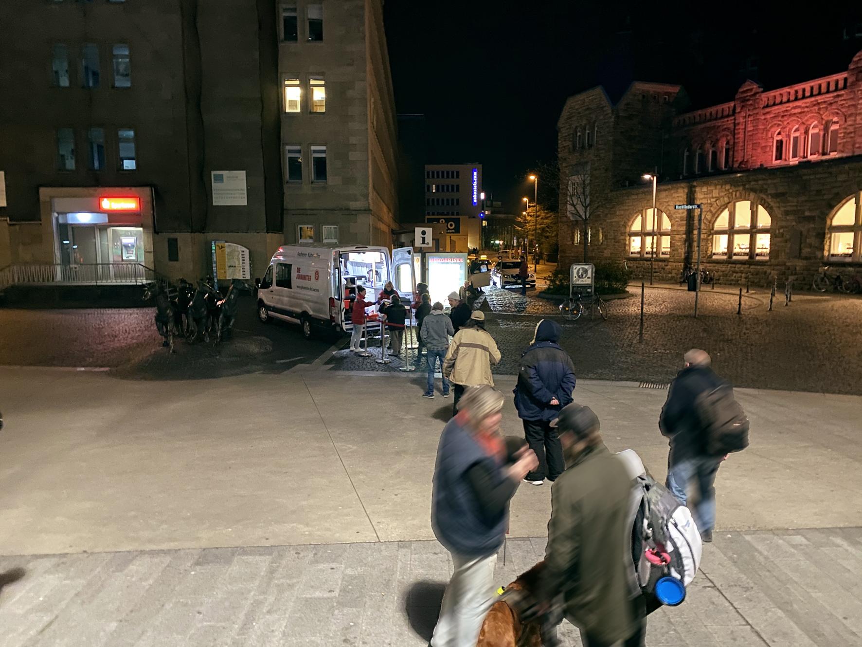 Obdachlose warten vor dem Aachener Hauptbahnhof auf die Ausgabe von warmem Essen