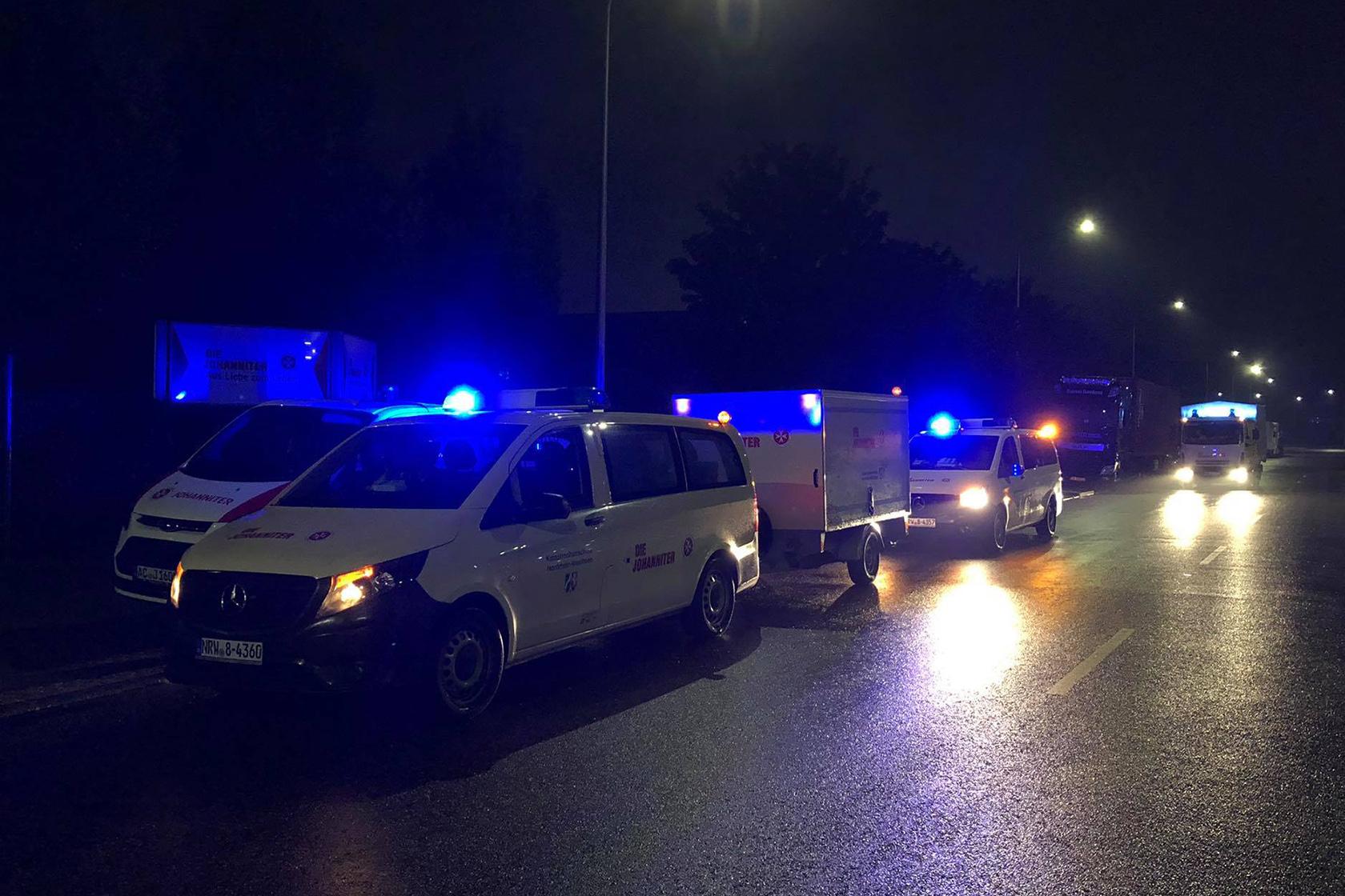Johanniter-Fahrzeuge mit Blaulicht im Dunkeln vor dem Ausrücken