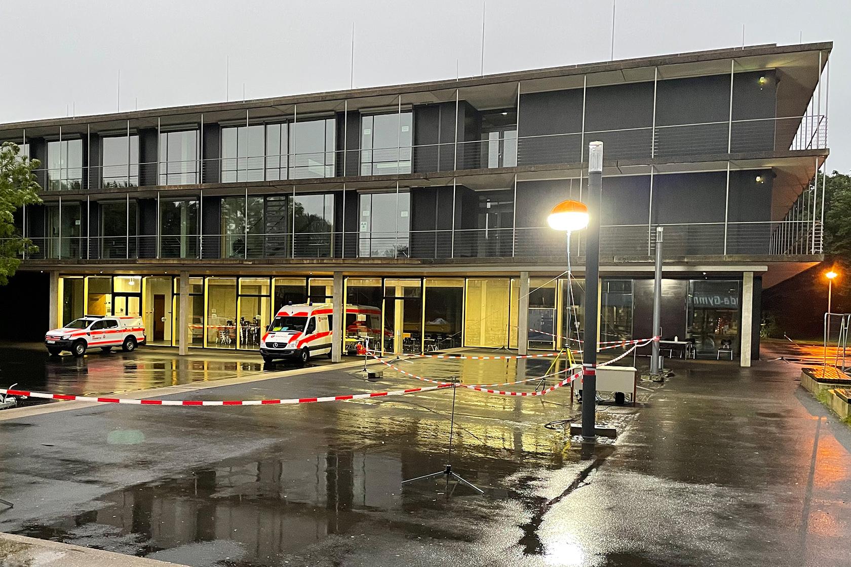 Erleuchtetes Schulgebäude mit Fahrzeugen des Bevölkerungsschutz auf dem regennassen Hof.