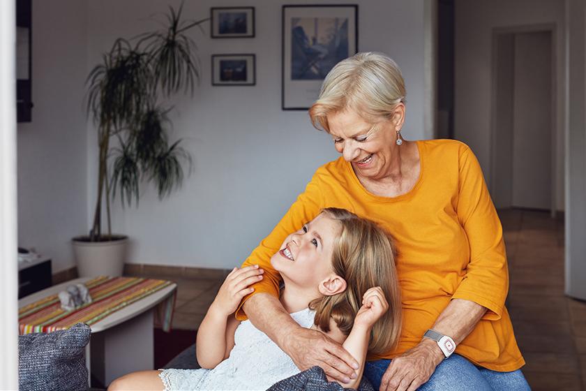Hausnotruf - Oma mit Hausnotrufarmband innig mit Enkelin