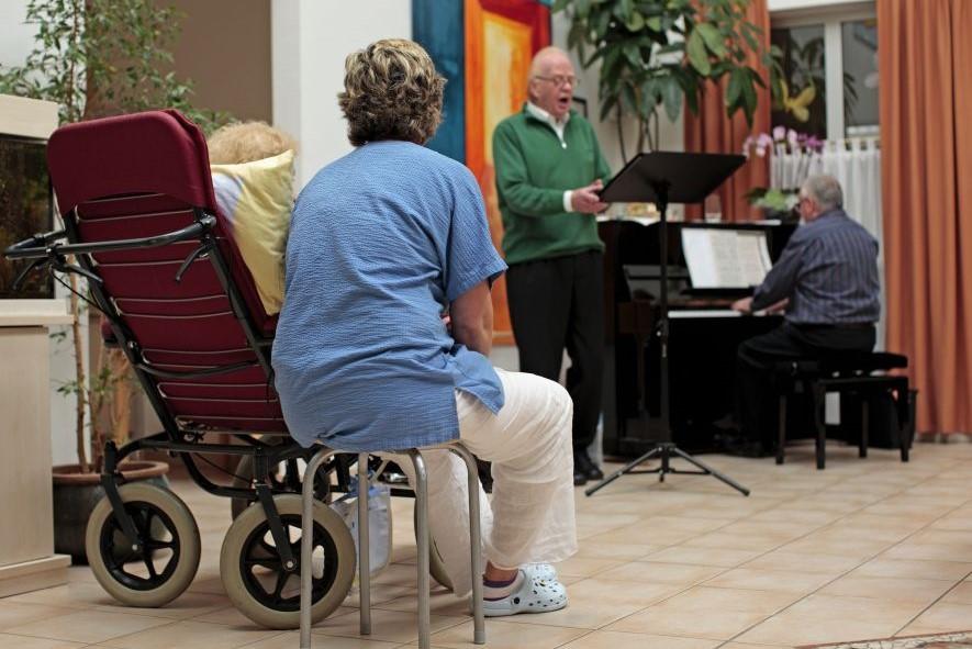 Eine Pflegerin sitzt neben einer Frau im Rollstuhl und hört einem Sänger zu.
