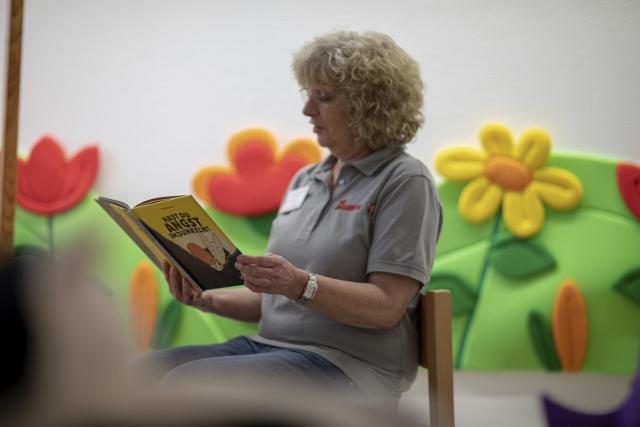 Eine Mitarbeiterin liest einem Kind aus einem Bilderbuch vor.