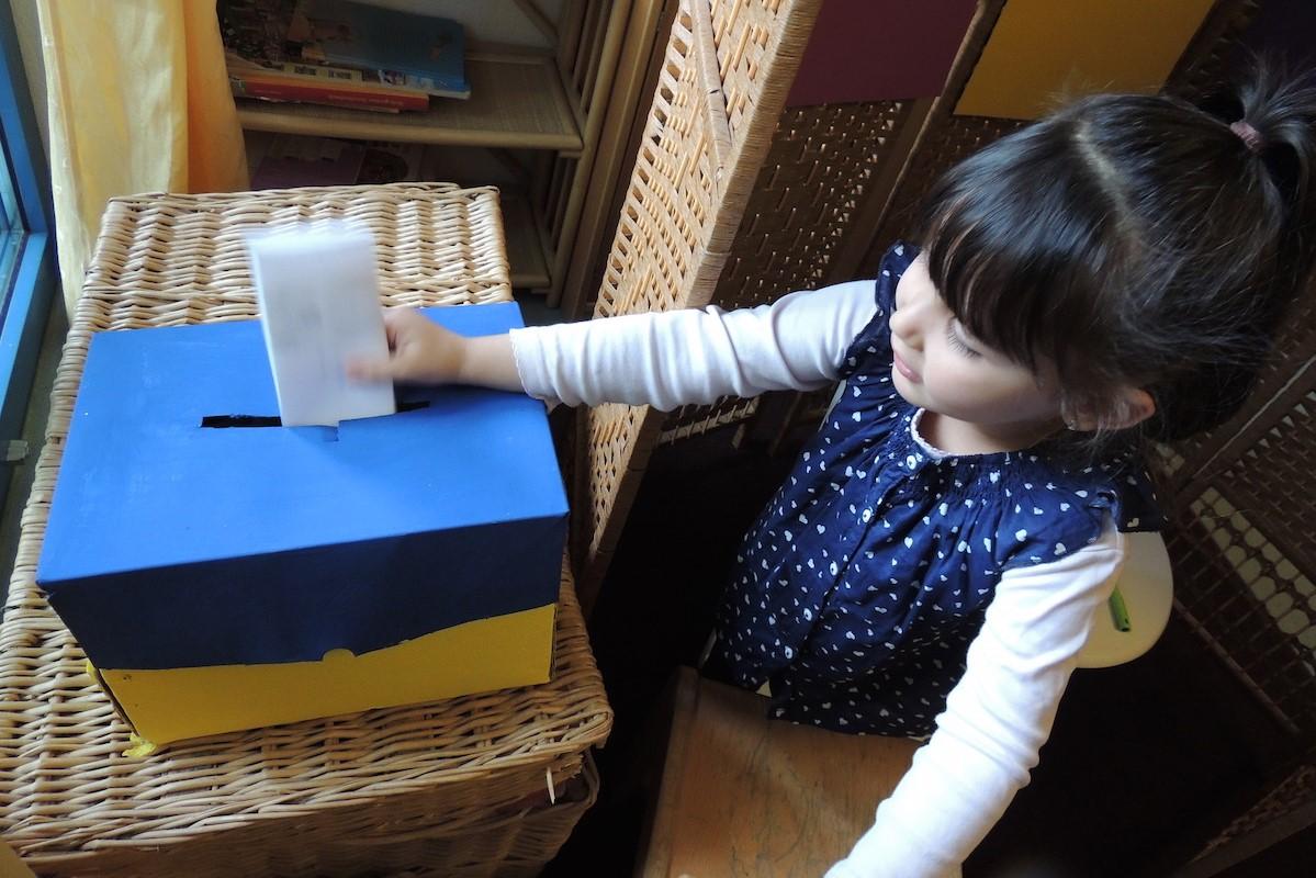 Ein Mädchen steckt einen Stimmzettel in eine Papp-Box.
