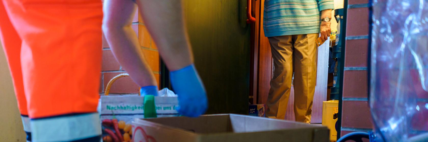 Helfer der Johanniter-Unfall-Hilfe beliefert eine ältere Frau mit Einkäufen während der Corona-Pandemie.