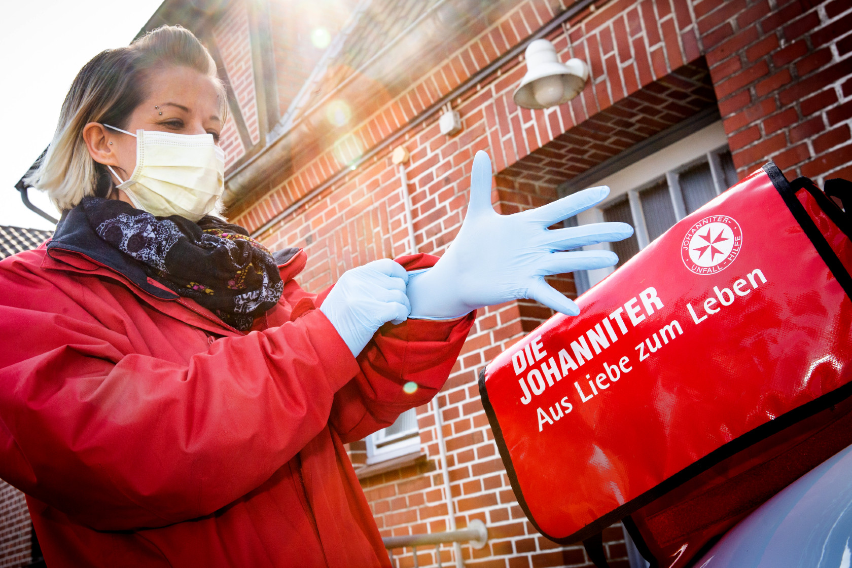 Eine Mitarbeiterin der Johanniter-Unfall-Hilfe legt sich Handschuhe und eine Atemmaske zum Schutz vor einer Corona-Infektion an.