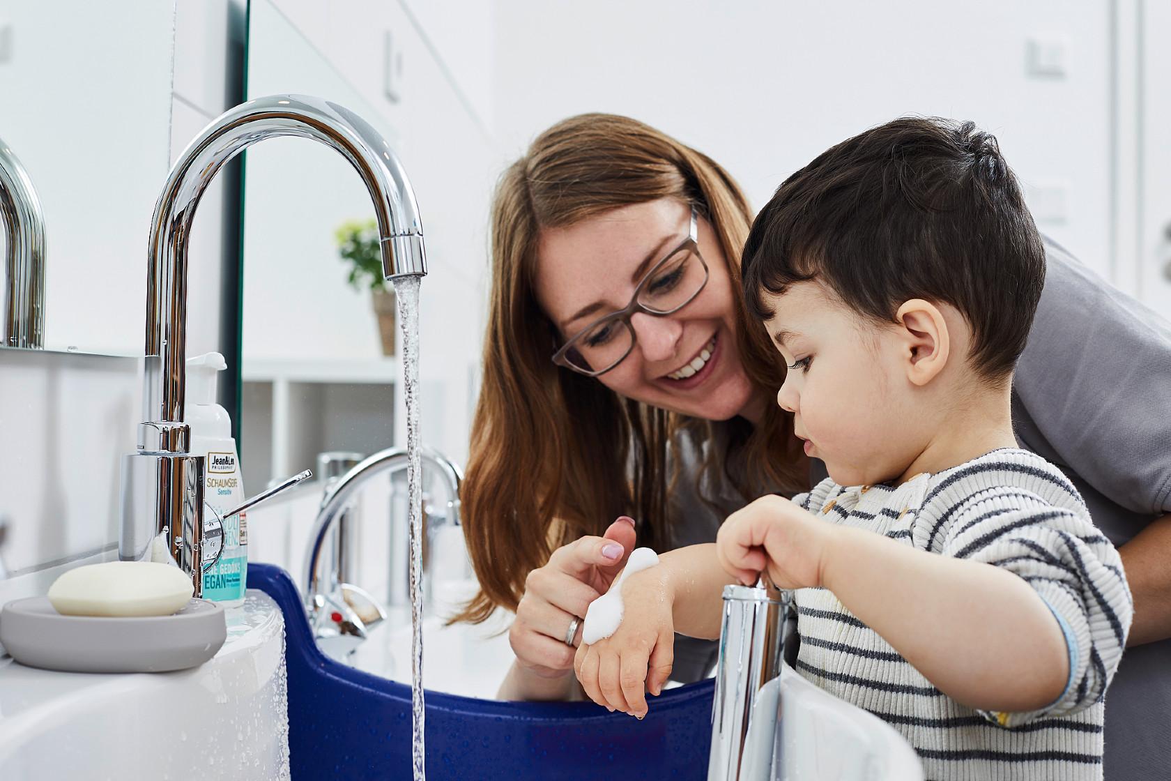 Eine Johanniter-Erzieherin beschäftigt ein Kita-Kind am Waschbecken.