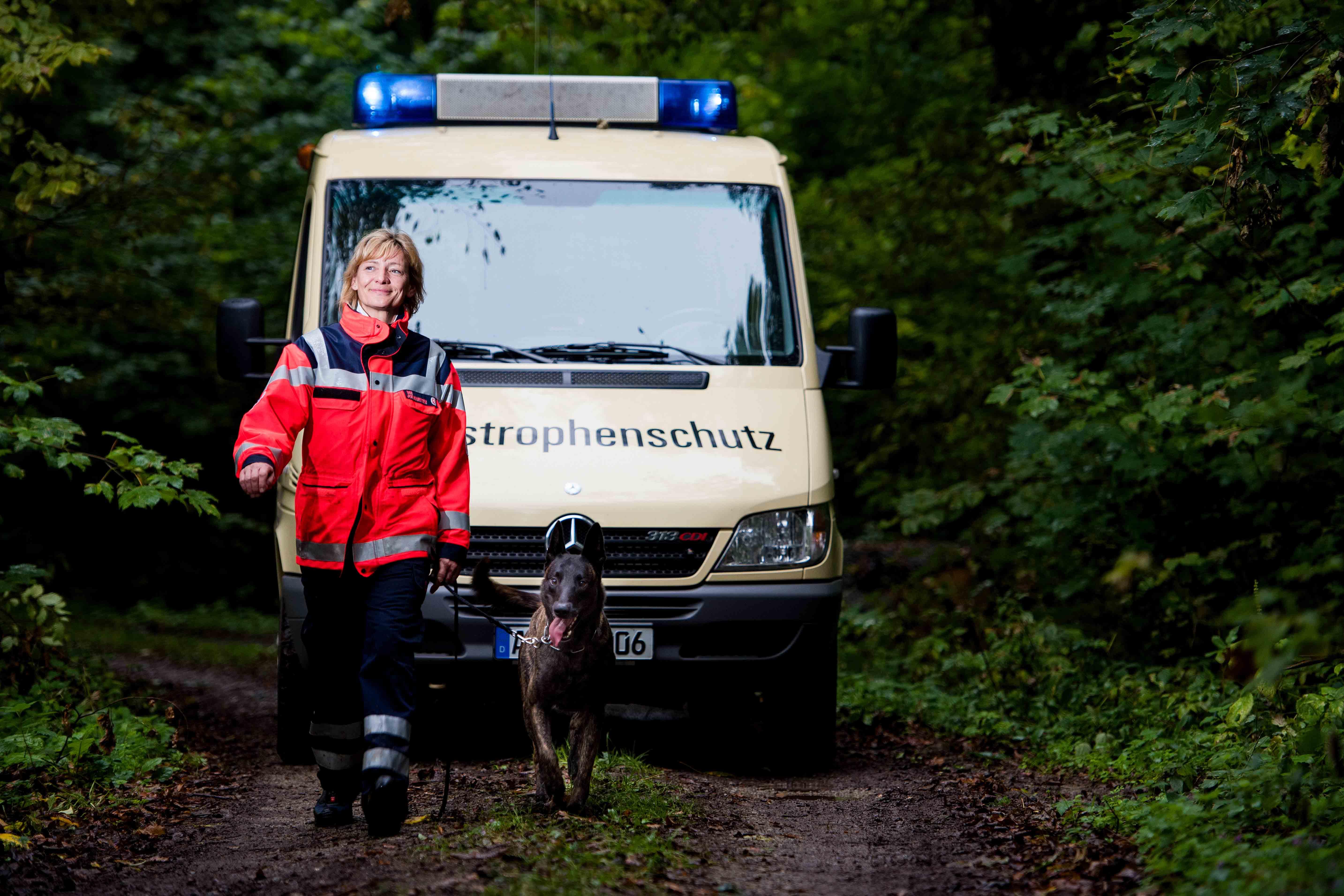 Ein Rettungshundeteam läuft im Wald. Dahinter fährt ein Auto des Katastrophenschutzes.