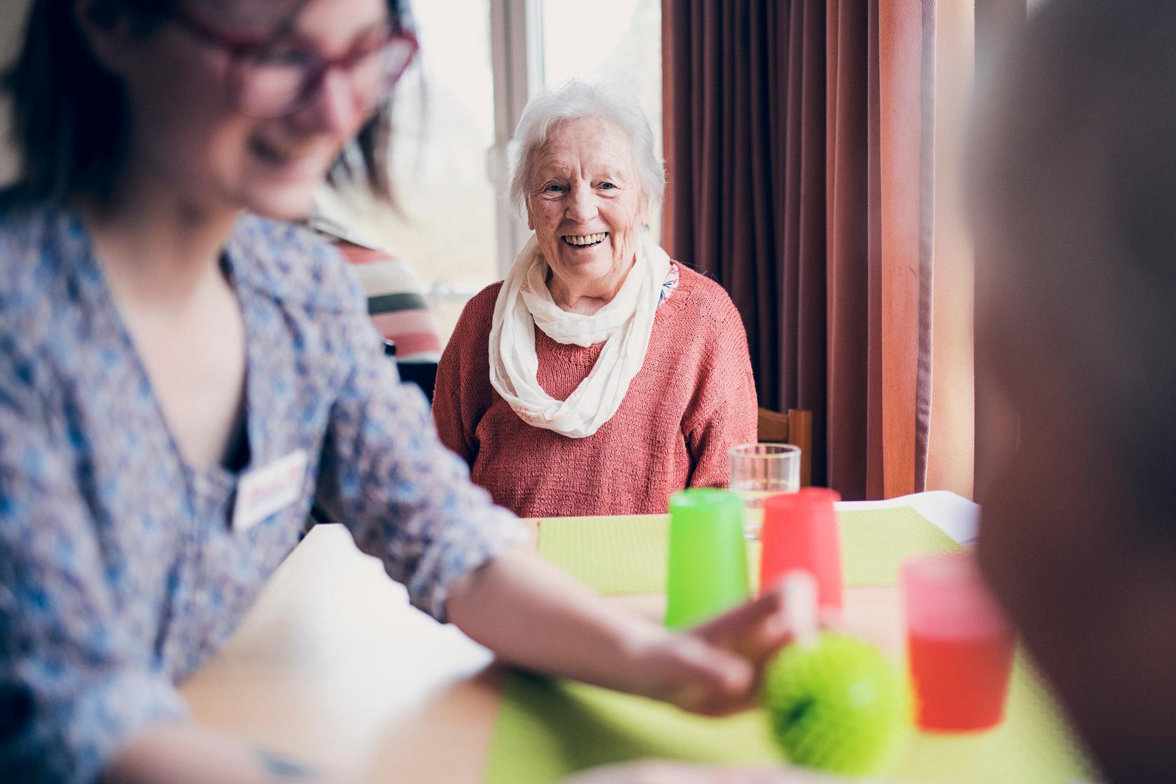 Eine Seniorin und eine Mitarbeiterin bei einem Spiel