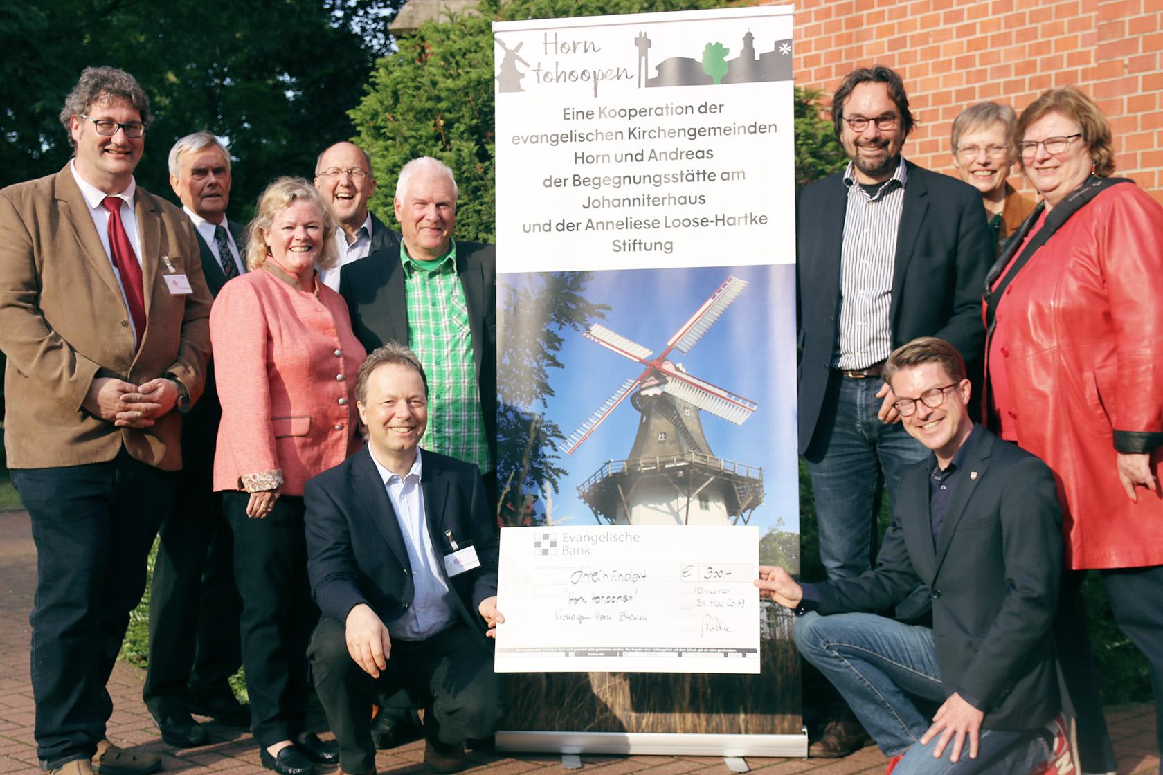 Menschen stehen und knieen um eine Roolup mit der Aufschrift Horn tohoopen und dem Foto einer Windmühle.