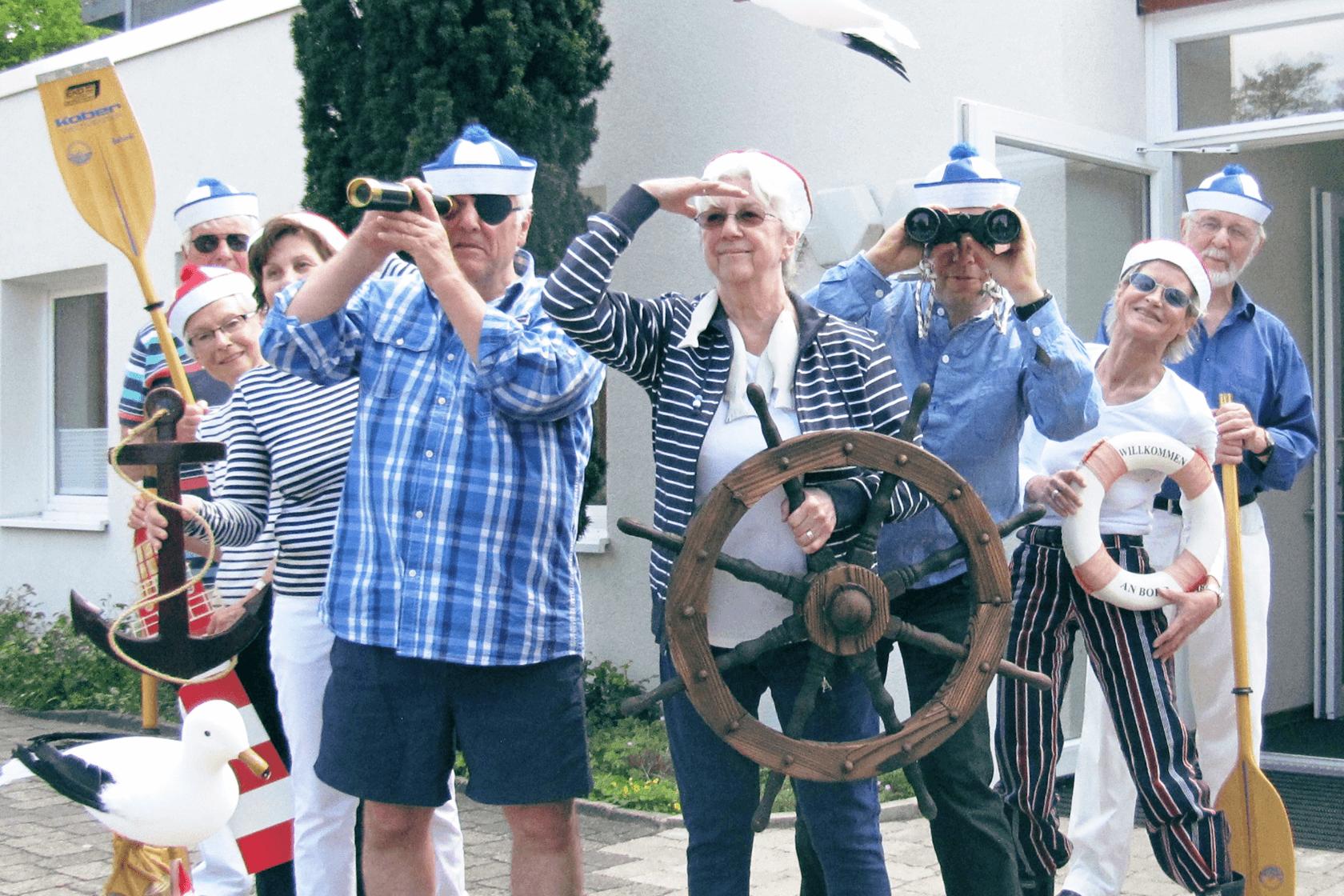 eine kleine Gruppe von Menschen illustriert mit blauweißer Kleidung und maritimen Requisiten ein Wochenthema im Begegnungszentrum