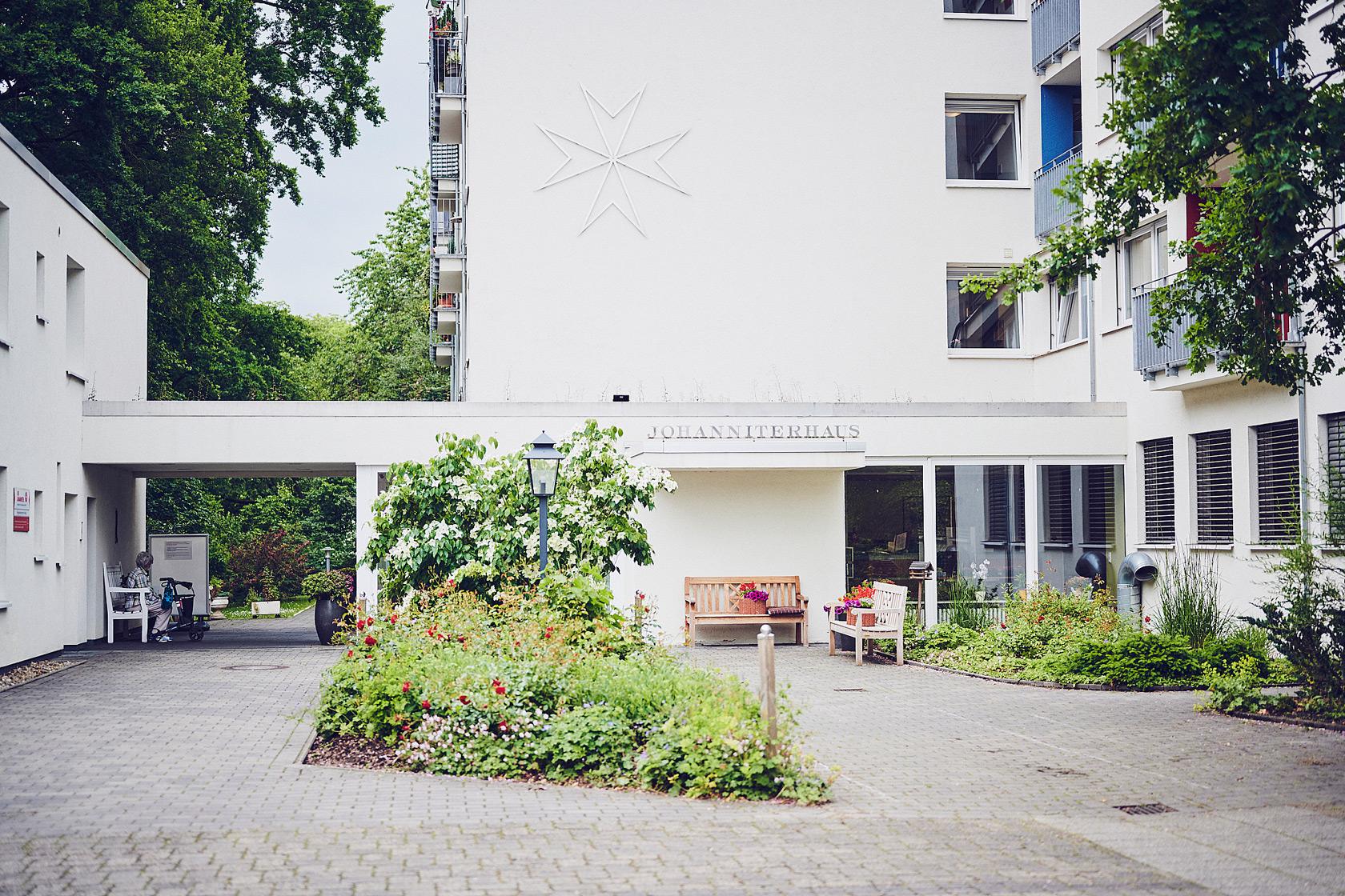 Auf dem Vorplatz des Einganges Johanniterhaus Bremen stehen Gartenbänke zur Nutzung gemeinsamer Treffs der Bewohner.
