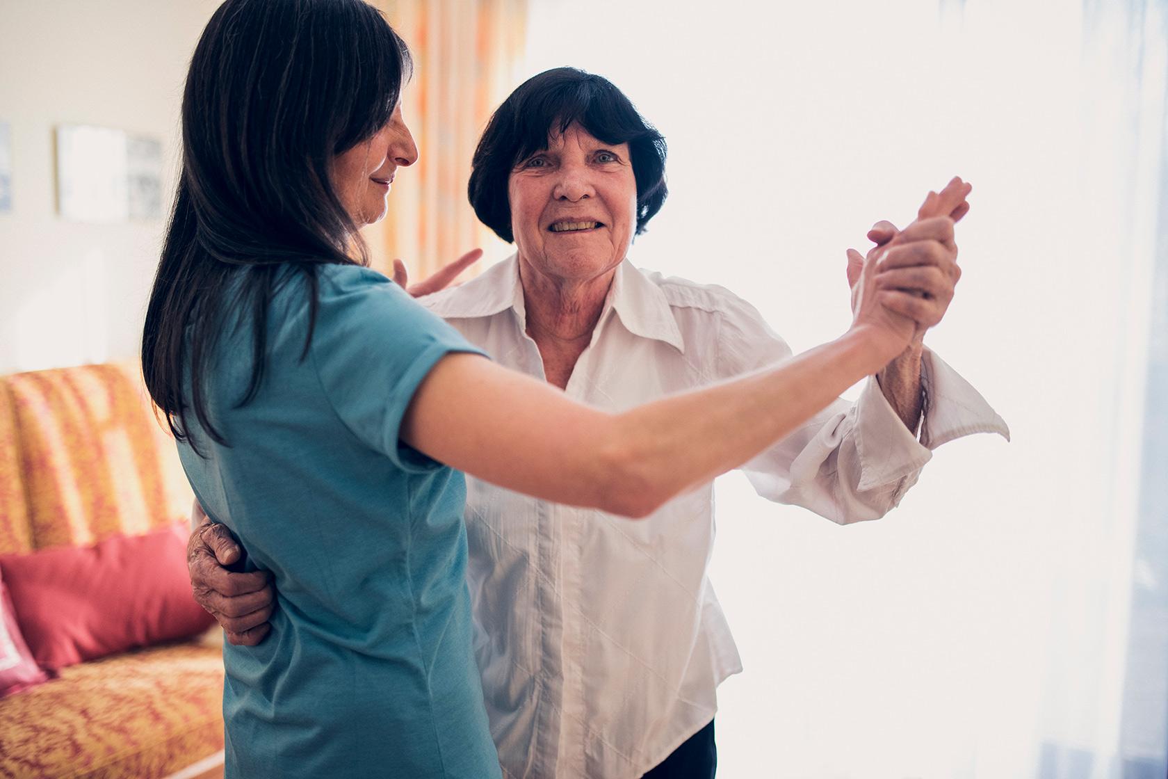 Eine Pflegerin tanzt mit einer Bewohnerin der Hausgemeinschaft