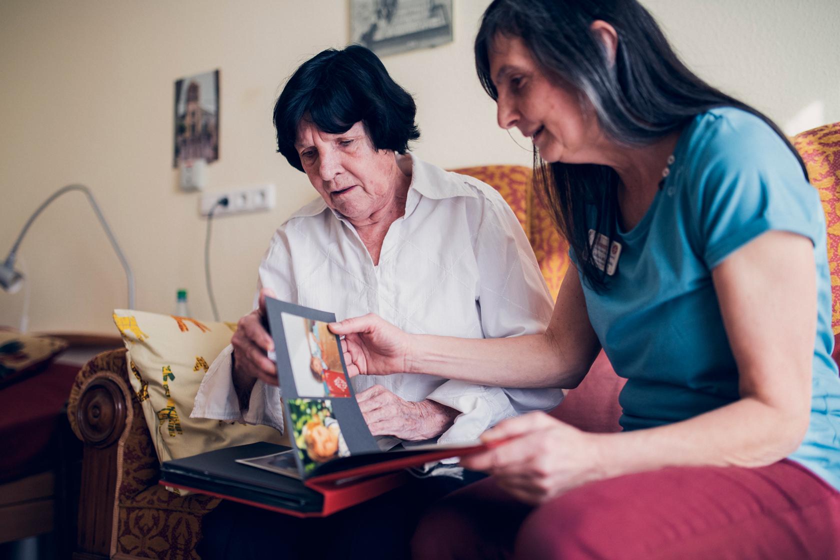 Eine Bewohnerin und eine Mitarbeiterin sitzen in einem Bewohnerzimmer auf einem Sofa und betrachten ein Fotoalbum.