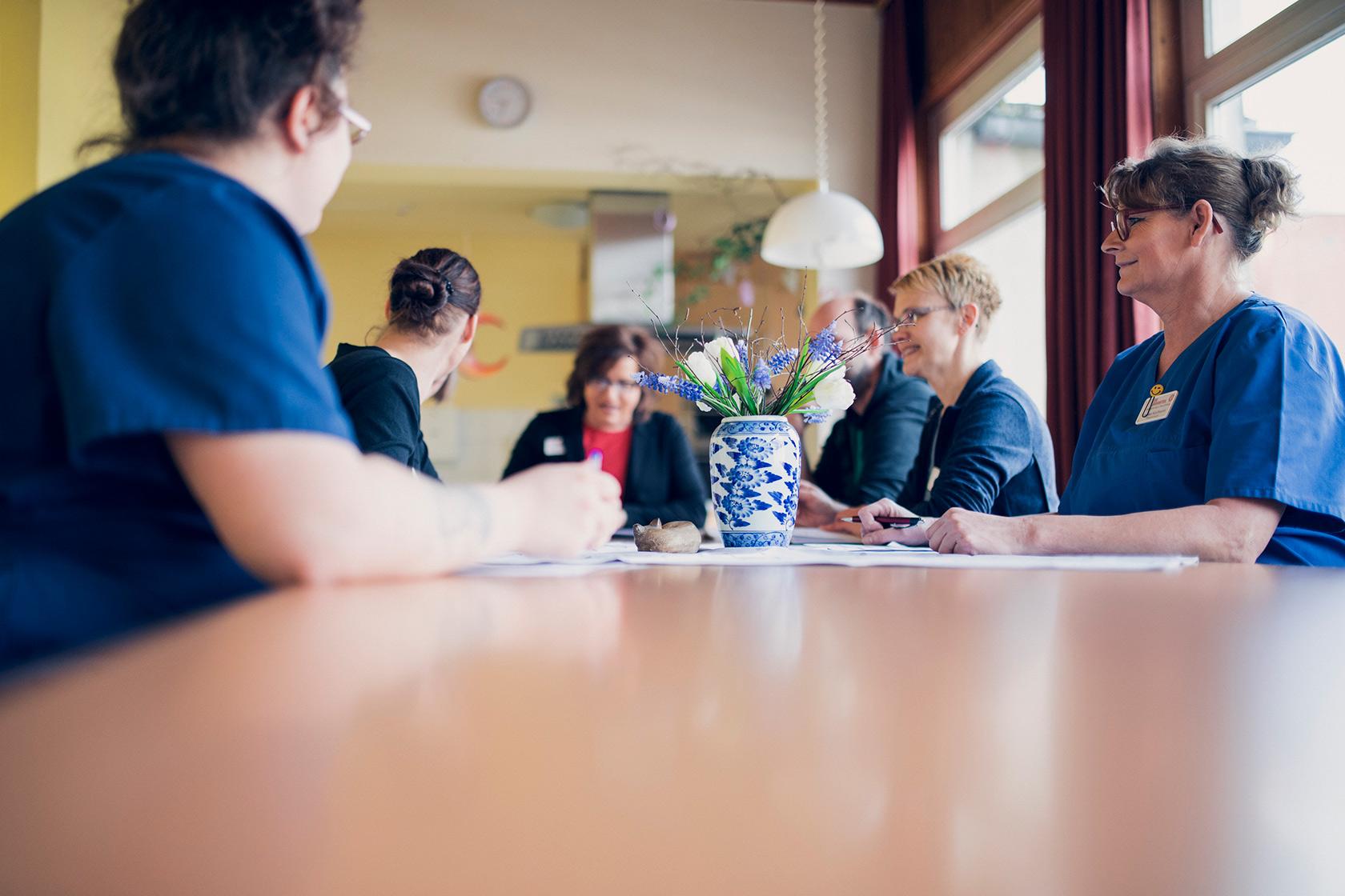 Mitarbeitende des Johanniterhaus Dannenberg sitzen an einem Tisch bei einer Besprechung