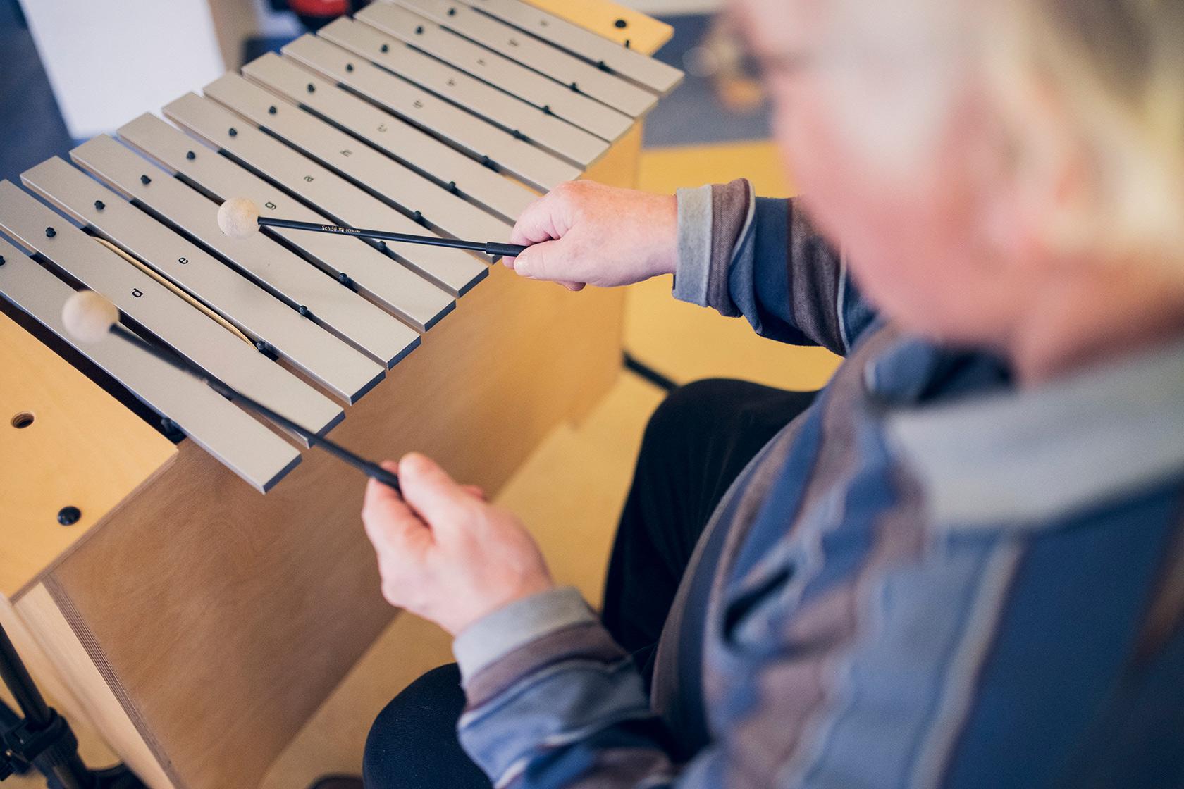 Eine Bewohnerin spielt ein Holzinstrument