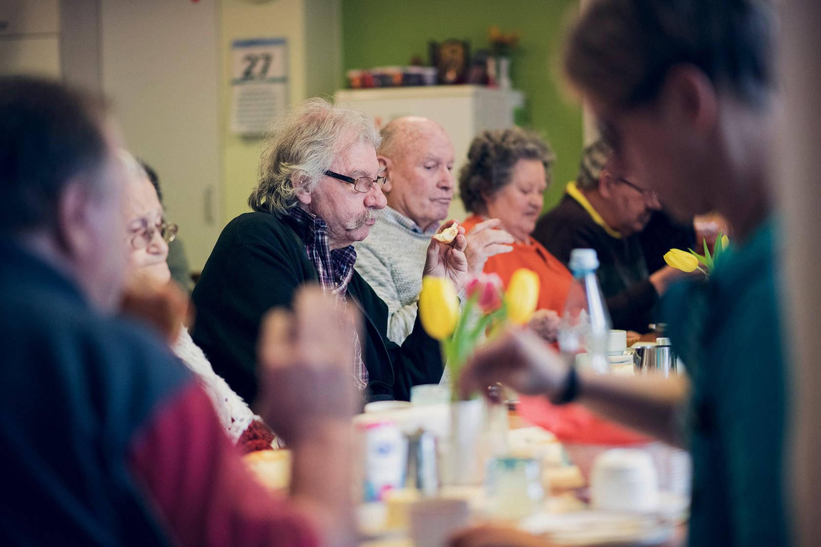 Eine Gruppe aus Bewohnenden frühstückt gemeinsam im Johanneshaus