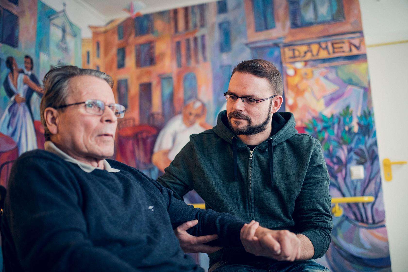 Ein jüngerer Mann im blauen Pullover hilft einem Bewohner des Johanneshaus Empelde
