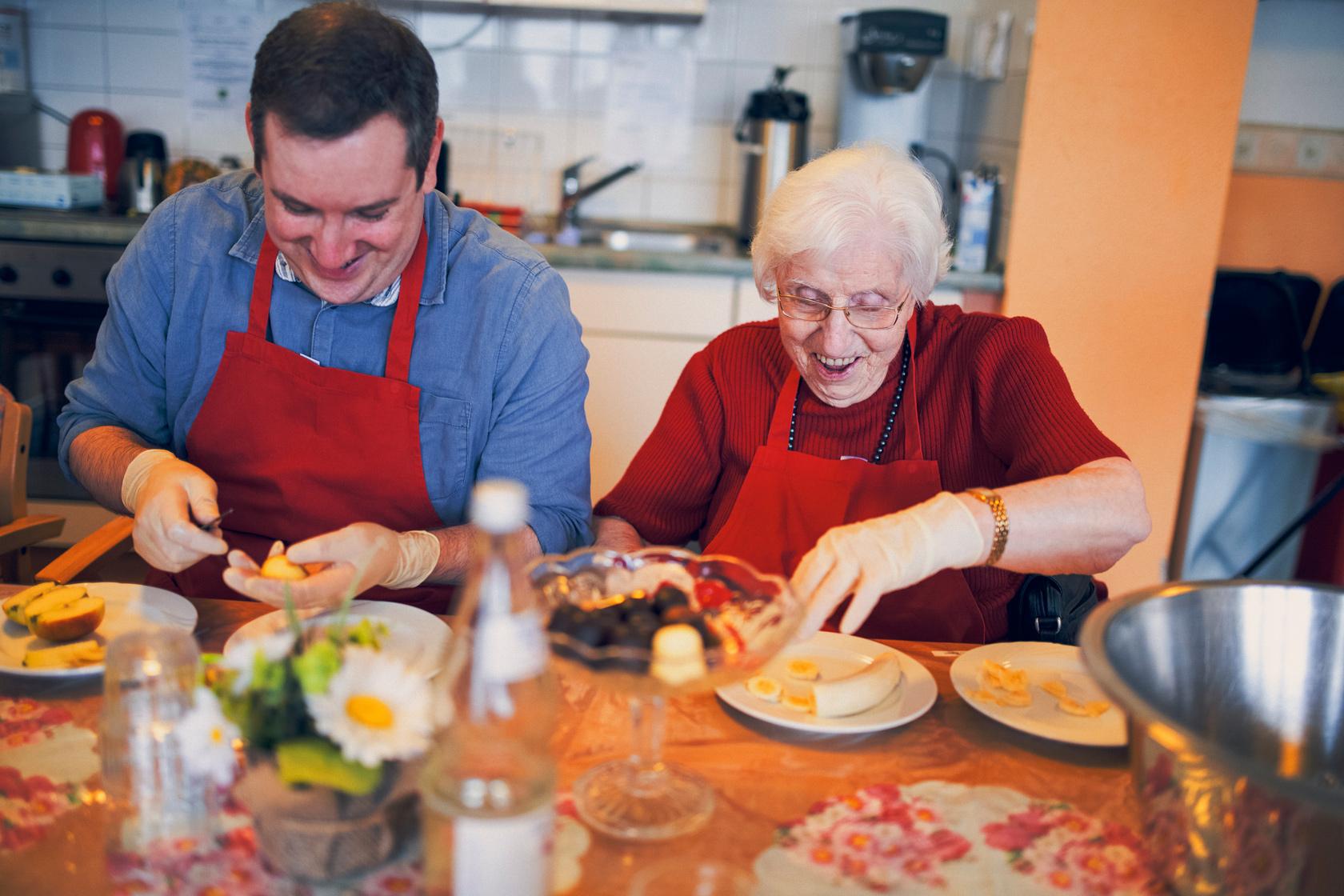 Seniorin hilft mit Freude beim Zubereiten des Nachtisches im Haus Lübeck
